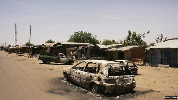 A burnt car is seen along a road in Buni Gari village in Nigeria's northeastern state of Yobe, 6 April 2014
