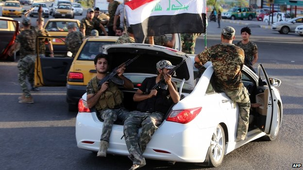 Iraqi Shia tribesmen parade with their weapons in central Baghdad's Palestine Street (17 June 2014)