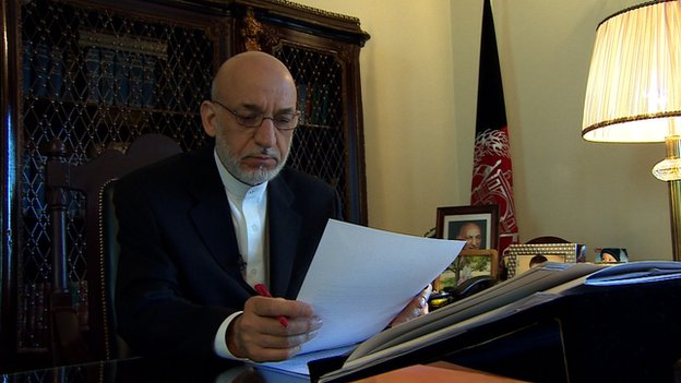 Hamid Karzai sits at his desk in June 2014
