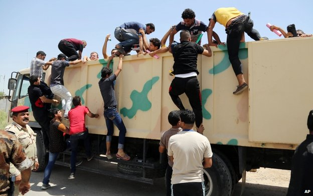 Young Iraqis board a lorry at a recruiting centre in Baghdad, 14 June