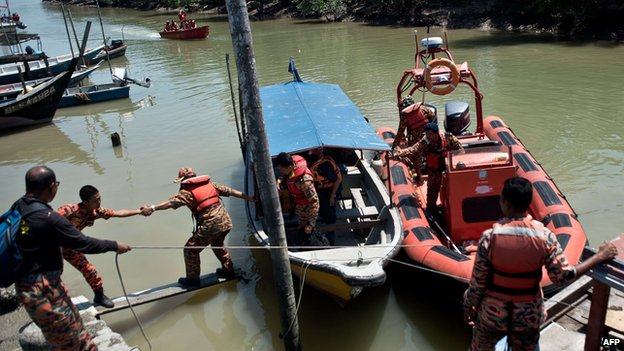 Malaysian search and rescue teams disembark from a boat after returning from a rescue mission on the outskirts of Banting on 18 June, 2014 after an apparently overloaded boat carrying Indonesian illegal migrants sank overnight in seas off western Malaysia