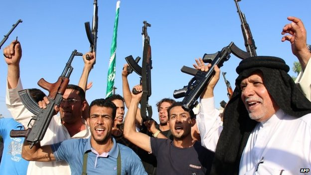 Iraqi men brandish their weapons as they show their willingness to join Iraqi security forces in Basra
