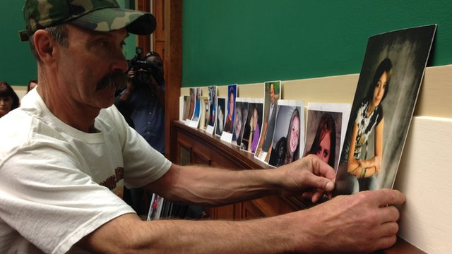 Randall Rademaker puts up a picture of his daughter, Amy Rademaker, w