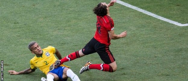 Brazil's Dani Alves challenges Mexico's Andres Guardado.