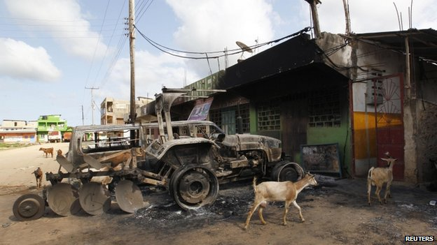 Goats roam around burnt-out cars and tractors in the coastal Kenyan town of Mpeketoni on 18 June 2014
