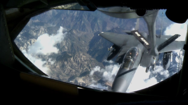An F-15 jet is refuelled in mid-air