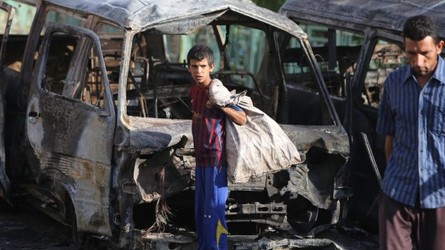 A boy stands in front of the wreckage of a car bomb in Baghdad on 18 June 2014