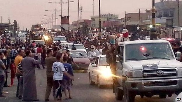 In this file still image posted on a militant Twitter account on Wednesday, June 11, 2014, which has been authenticated based on its contents and other AP reporting, militants parade down a main road in Mosul, Iraq.