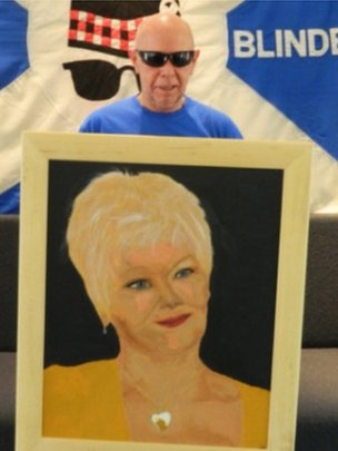 A picture of Derek O'Rourke holding his painting of Judi Dench
