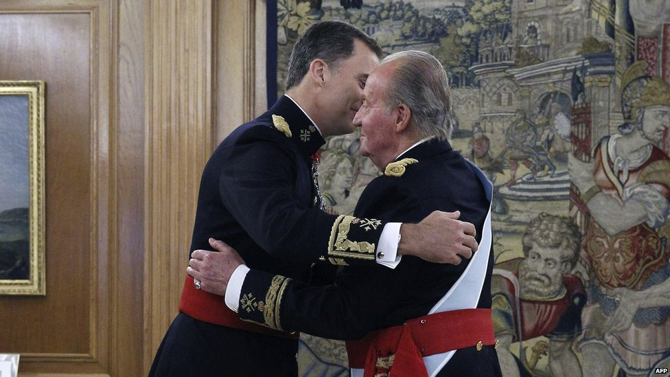 Spain's King Felipe VI (left) hugs his father Juan Carlos during a handing over ceremony for the sash signifying the leadership of the military at the Zarzuela Palace in Madrid on 19 June 2014