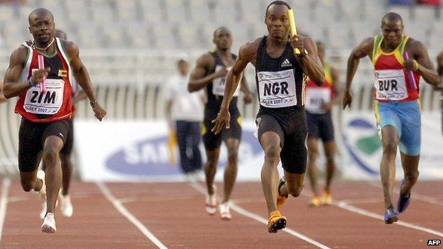 Nigeria's Metu Obina (C), runs between Zimbabwe's Lewis Banda (L) and Burkina Faso's Idrissa Sanou (R) to win the Men's 4 x 100 relay final on 20 July 2007 at the All-African-Games in Algiers