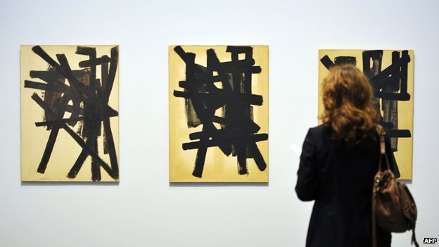 A woman looks at some of Pierre Soulages' paintings