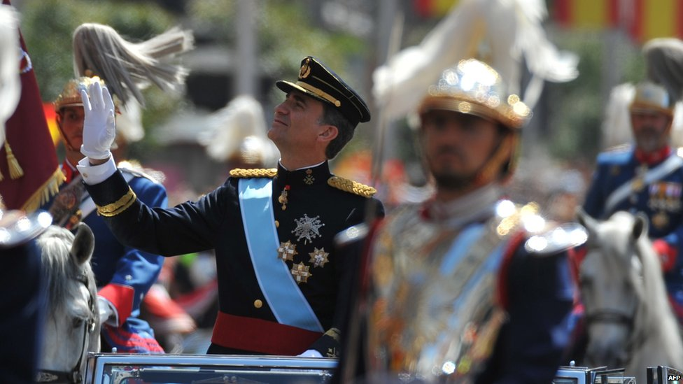 Spain's King Felipe VI waves in the motorcade on his way from the Congress of Deputies to the Royal Palace in Madrid on 19 June 2014