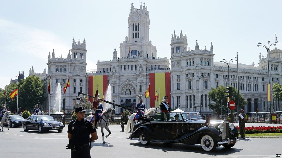 Spain's King Felipe VI Queen Letizia ride in a vehicle through Plaza de Cibeles on their way from the Congress of Deputies to the Royal Palace in Madrid on 19 June 2014
