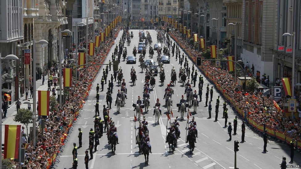 A general view shows Spain's new King Felipe VI and his wife Queen Letizia as they parade by car through the streets of Madrid on 19 June 2014