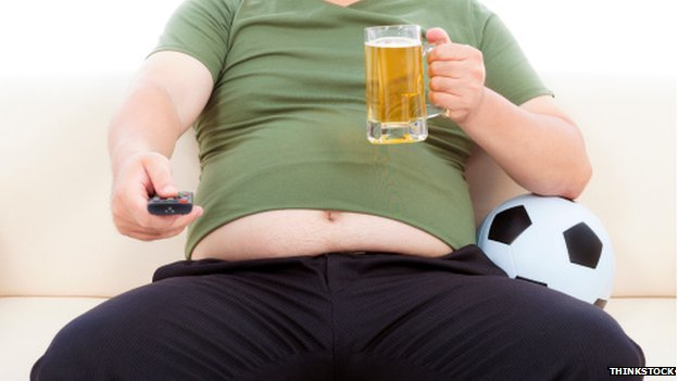 Man on sofa with remote and beer