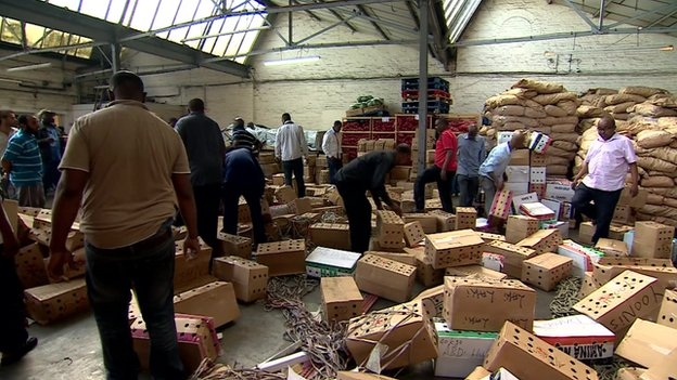 Men working among boxes of khat in west London depot