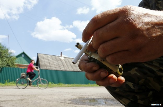 A rebel fighter holds a grenade and a cigarette in Siversk, near Krasnyy Liman, 19 June