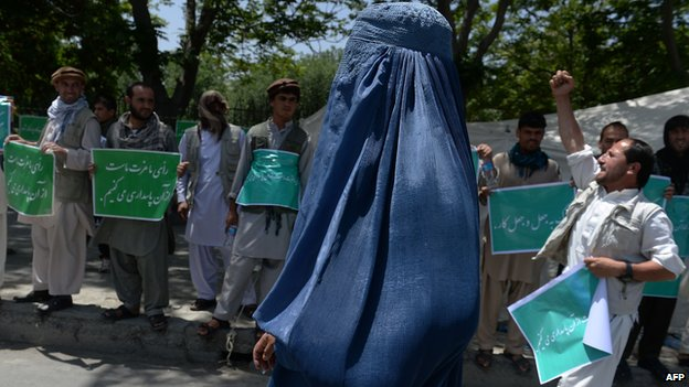 A burqa-clad Afghan woman walks past demonstrators as they shout slogans in support of presidential candidate Abdullah Abdullah in Kabul on 19 June 2014.