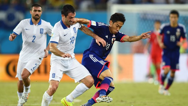 Greece's Georgios Karagounis battles with Japan's Shinji Kagawa