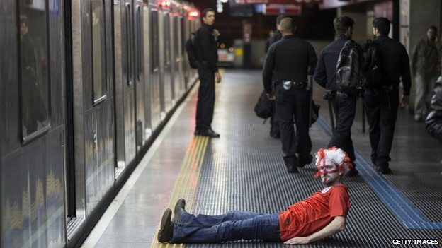 "A fan of the England football team lies on the platform of Pedro II Metro station after Uruguay""s 2-1 victory over England (19 June 2014)"