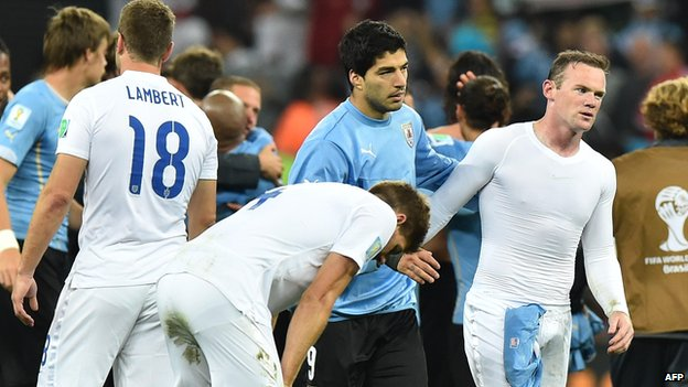 England players are consoled by Uruguay's forward Luis Suarez after defeat in the World Cup Group D football match between Uruguay and England on 19 June 2014