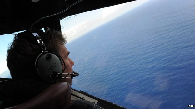 In this file photo taken on April 13, 2014 from a Royal New Zealand Airforce P-3K2-Orion aircraft, co-pilot and Squadron Leader Brett McKenzie helps to look for objects during the search for missing Malaysia Airlines flight MH370