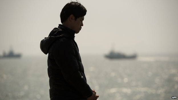 A relative of a passenger on board capsized South Korean ferry Sewol prays at an area where family members of victims of the disaster are gathered at Jindo harbour on 22 April, 2014