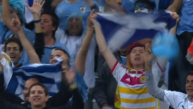 A Scotland fan shows his colours in the Uruguay end