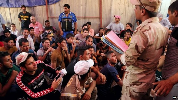Iraqi men check in at main army recruiting centre to volunteer for military service in Baghdad, Iraq, Friday, June 20, 2014,