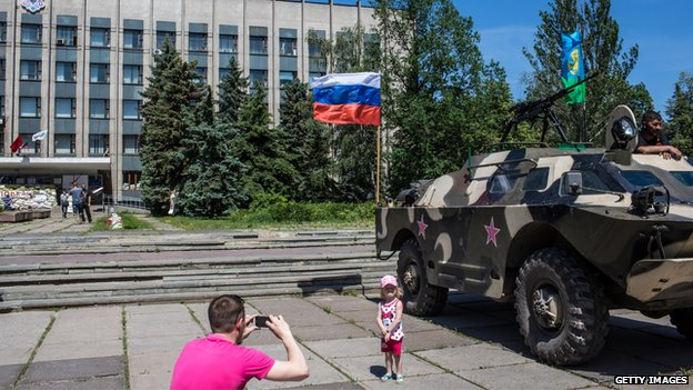 A man photographs his daughter in front of a military vehicle in Horlivka (Gorlovaka)