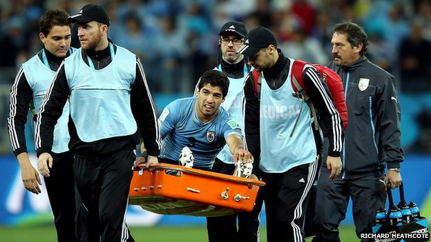 Luis Suarez being taken off the pitch against England