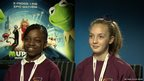 Two female School Reporters in front of Muppets poster