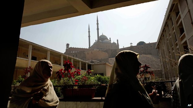 Women pass by the mosque of Mohammed Ali in Cairo
