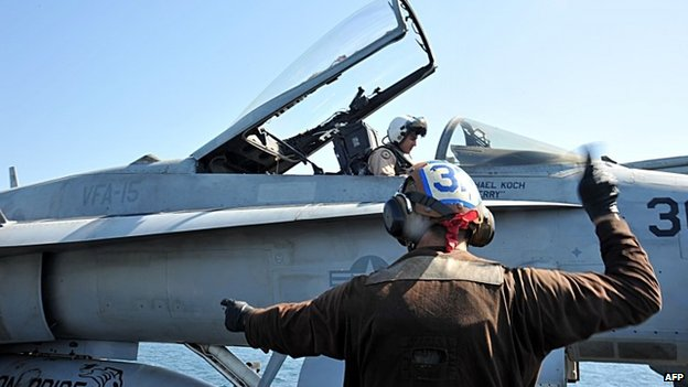 US Navy photo show a sailor making checks on an F/A-18C Hornet aboard the aircraft carrier USS George HW Bush on 18 June 2014, in The Gulf.
