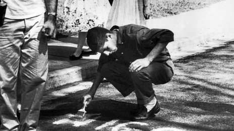 An American student paints over a racist slur outside a school in 1957