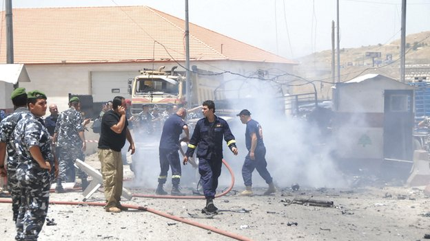 Firefighters put out a fire as policemen secure the site of an explosion at the Dahar al-Baidar area in Lebanon's Eastern Bekaa Valley on 20 June 2014.