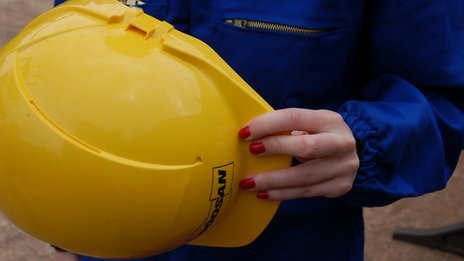 Nail varnished hand with hard hat