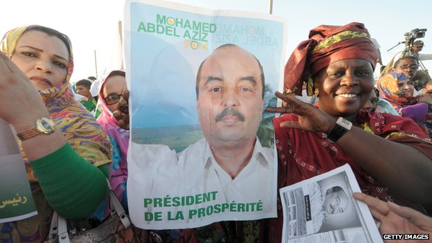Supporters of Mauritania's president and candidate to his succession Mohamed Ould Abdelaziz hold campaign posters during a meeting in Akjoujt