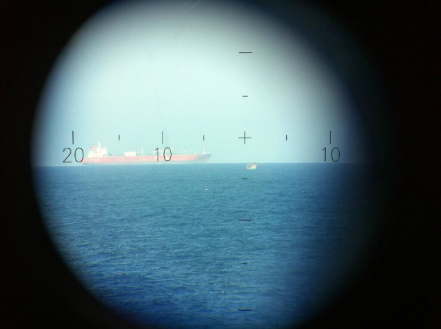 The view through from an Italian navy vessel of a boat carrying migrants near two large tankers in the Mediterranean - 20 June 2014