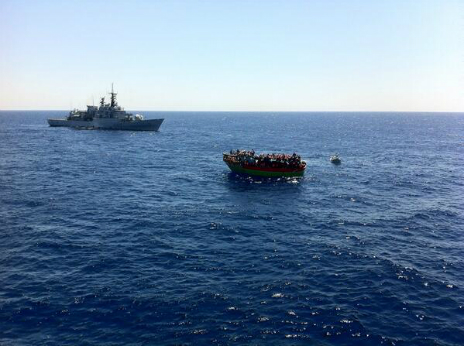 An Italian navy vessel moves in to rescue migrants stranded on a small boat in the Mediterranean - 20 June 2014