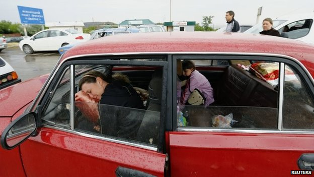 A woman and a child rest inside their car as they wait in a queue to leave Ukraine