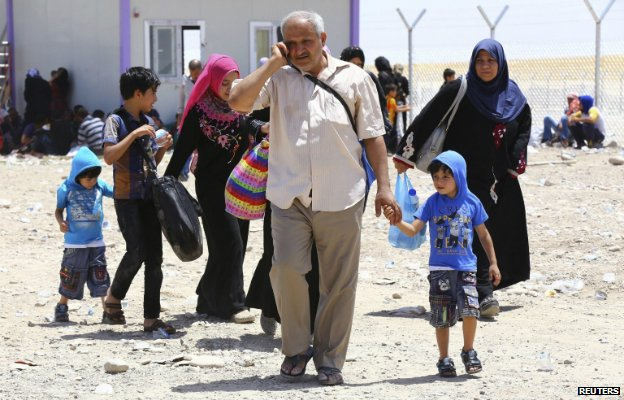 A family fleeing Mosul arrive at a checkpoint on the outskirts of Irbil - 10 June 2014