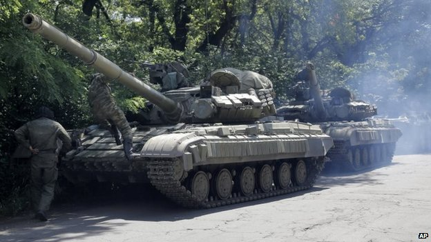 Pro-Russian troops prepare to travel in a tank on a road near the town of Yenakiyevo, Donetsk region, eastern Ukraine, Friday, June 20, 2014.