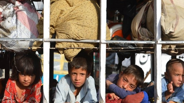Pakistani children arrive by truck with some belongings in the neighbourhood of Bannu, after fleeing North Waziristan tribal region in north-western Pakistan