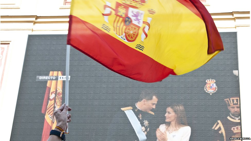 Spanish flag waving in front of a live broadcast of King Felipe VI of Spain being proclaimed head of state.