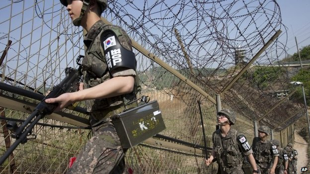 South Korean army soldiers patrol along the barbed-wire fence at the demilitarized zone (DMZ) in Cheorwon, South Korea in May 2014