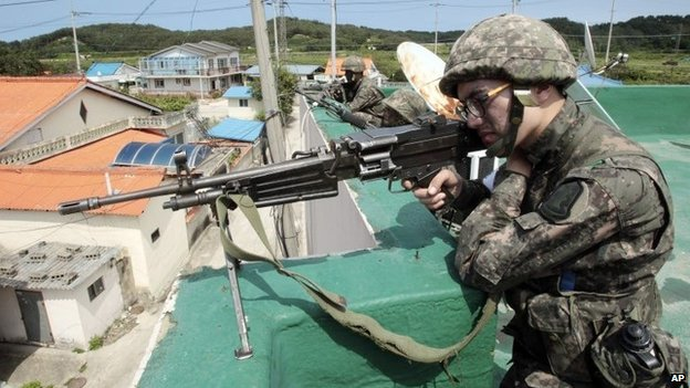 A soldier aims his weapon in Goseong, South Korea, 22 June 2014