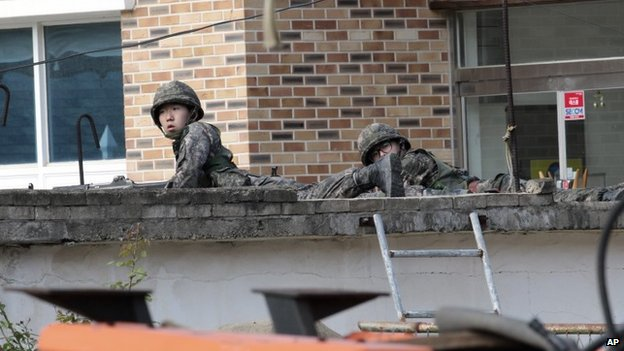 Troops take position as they search for a renegade South Korean soldier in Goseong, South Korea, 22 June 2014