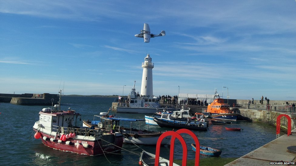 A military plane performs an aerial display over a lighthouse in Donaghadee Harbour, County Down, Northern Ireland as part of Armed Forces Day.  Photo by: Richard Beattie.